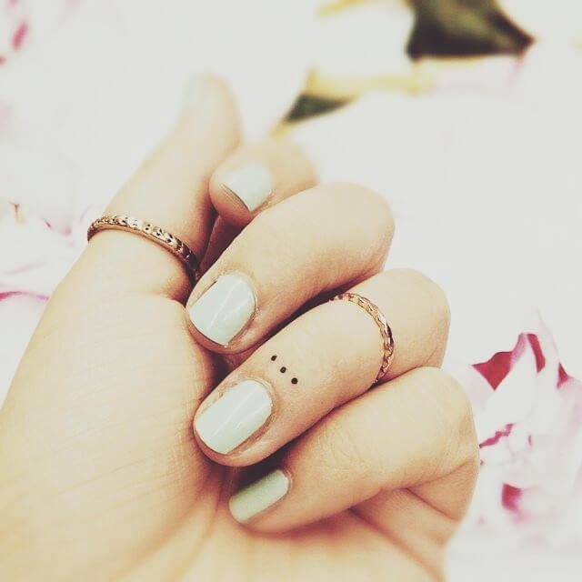Kleines Tattoo Dreo Punkte auf dem Finger