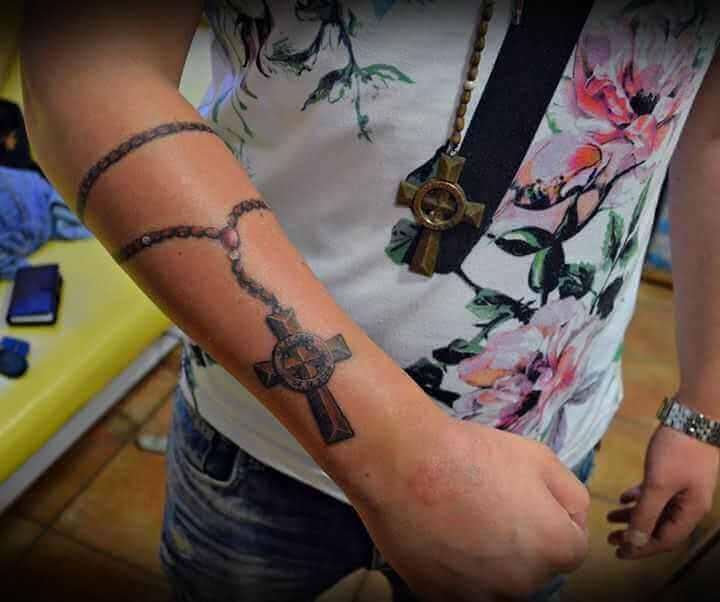 Kreuz an Ketter auf Arm