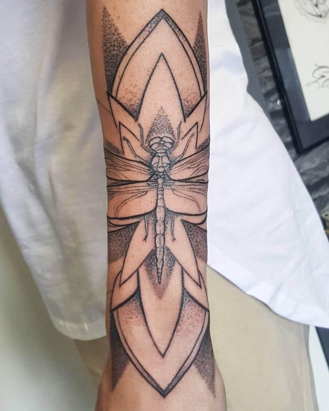 Libelle mit Blume auf dem Unterarm